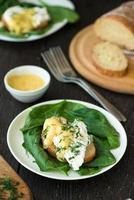 huevo escalfado sobre un trozo de pan con espinacas