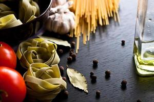 Italian tagliatelle pasta on wooden background