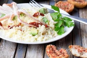 Couscous with seafood, dried tomatoes, avocado and little toast