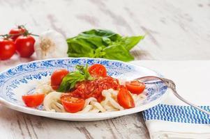 plato saludable de espagueti italiano cubierto con un sabroso tomate foto