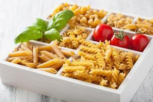 various raw wholegrain pasta in white wooden box photo