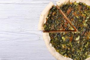 pie with herbs, cheese and spinach close-up top view