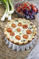 tarta con tomates cherry y cebolla en una fuente de aluminio para hornear foto