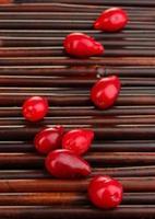 bayas frescas de cornel en estera de bambú foto