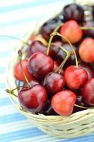 Primer plano de cerezas frescas y dulces maduras en cesta de mimbre foto