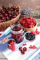 Berries jam in glass jar on table, close-up photo