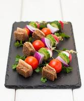 Appetizer with herring, rye bread and vegetables on skewers photo