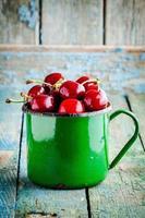 cerezas jugosas maduras en la taza vieja foto