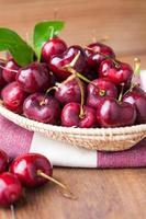 Many fresh cherries in bamboo basket photo