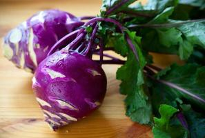 Purple kohlrabi with foliage on a wooden board