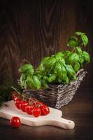 hierbas frescas en cesta rústica y tomates en tabla de cortar foto