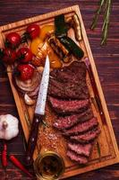 BBQ steak with grilled vegetables on cutting board