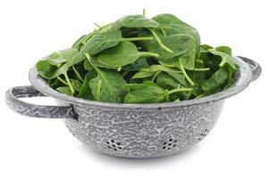 fresh spinach leaves in an enamel colander