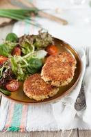 Quinoa patties on a brown plate with fresh salad