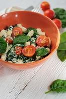 Ensalada con pasta, espinacas, tomates cherry y ricotta en blanco foto