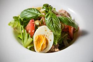 plate of spring mix salad with strawberry, eggs and tuna photo