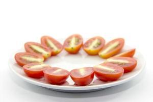 seção transversal de mini tomate fatiado em chapa branca