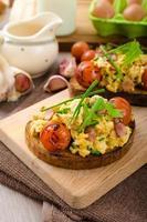 huevos revueltos con tocino de bruja, hierbas y tomate