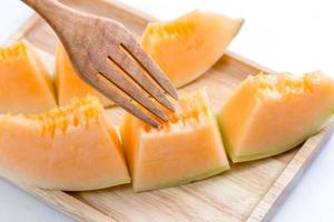 Juicy cantaloupe melon with fork on a wooden plate photo