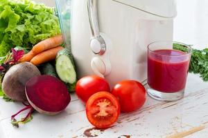 Selection of vegetables and beet juice, white wood background photo