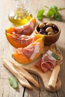 cantaloupe melon with prosciutto grissini olives. italian appeti photo