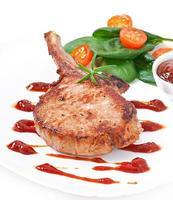 Juicy grilled pork fillet steak with greens