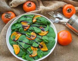 spinach salad and persimmon photo