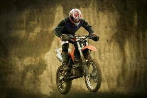 Motocross enduro rider jumping with motorcycle photo