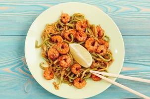 shrimps and zucchini noodles in green plate on blue
