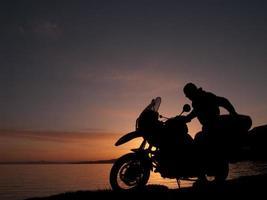 silueta de motociclista en el atardecer más cerca foto