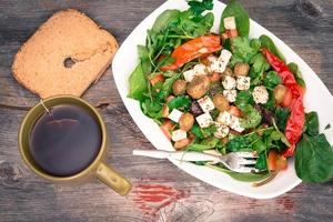 Dish of baby spinach salad with bread and tea photo