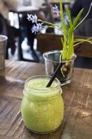 batido de desintoxicación verde presentado en un frasco de vidrio con una pajita