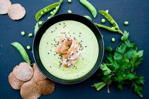 Healthy green soup with ham and peas