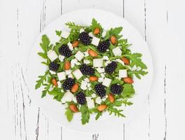 Green salad with arugula, melon, blackberries, almonds and feta cheese
