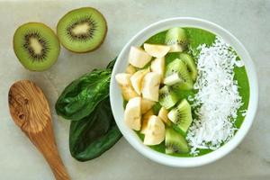 Green smoothie bowl with spoon on white marble photo
