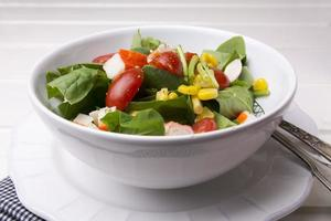 spinach salad with cherry tomatoes and corn in bowl