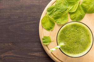 Healthy green smoothie on rustic wood background