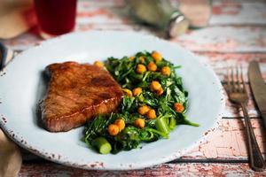 bife fresco com salada verde sobre fundo de madeira rústica