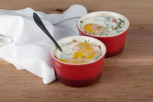 Eggs baked with creamy sauce, mushrooms, ham, cheese and herbs photo