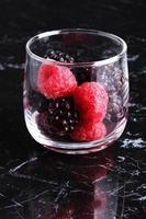 raspberry and blackberry, frozen berries on marble background