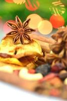 christmas spices, nuts, cookies and dried fruits on bokeh background