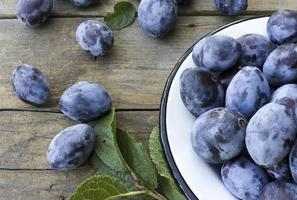 Fresh plums on wooden background photo