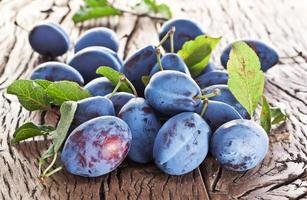 Plums on an old wooden table. photo