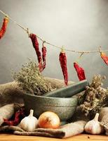 dried herbs in mortar and  vegetables on grey background photo