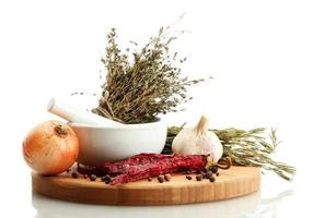 dried herbs in mortar and vegetables, isolatrd on white photo