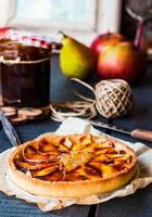 round apple tart with pear jam and caramel, vertically photo
