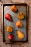 Bosc et poires rouges sur une plaque à pâtisserie sur table en bois