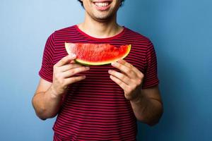 Young multiracial man with a slice of watermelon