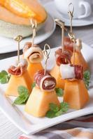 Italian appetizer: melon with ham on skewers vertical