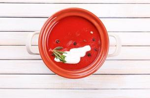Tasty tomato soup on wooden table photo